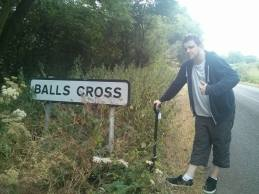 """BALLS CROSS: """"Why is he holding a spade?"""" you ask. He is holding a spade because there was an obstructive amount of foliage in front of the sign. Mark bashed the foliage away with a spade. We got our picture."""